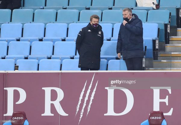 BIRMINGHAM, ENGLAND - JANUARY 23: Dean Smith, Manager of Aston Villa (R) looks on from the stands during the Premier League match between Aston Villa and Newcastle United at Villa Park on January 23, 2021 in Birmingham, England. Sporting stadiums around England remain under strict restrictions due to the Coronavirus Pandemic as Government social distancing laws prohibit fans inside venues resulting in games being played behind closed doors. (Photo by Mike Egerton - Pool/Getty Images)