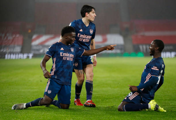 SOUTHAMPTON, ENGLAND - JANUARY 26: Bukayo Saka of Arsenal celebrates with Hector Bellerin and Nicolas Pepe after scoring their team's second goal during the Premier League match between Southampton and Arsenal at St Mary's Stadium on January 26, 2021 in Southampton, England. Sporting stadiums around the UK remain under strict restrictions due to the Coronavirus Pandemic as Government social distancing laws prohibit fans inside venues resulting in games being played behind closed doors. (Photo by Frank Augstein - Pool/Getty Images)
