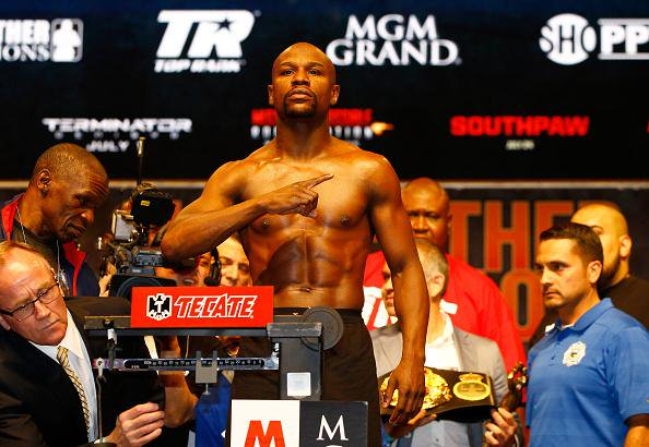 The showoff: Floyd Mayweather (pictured, middle) poses for press pictures during his pre-bout weigh-in, on Friday evening.
