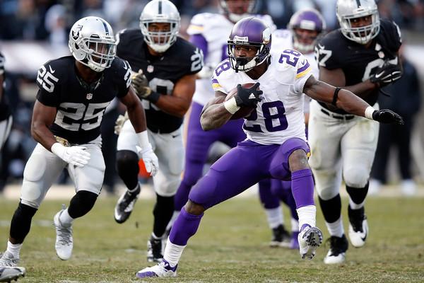 Adrian Peterson runs against the Oakland Raiders
