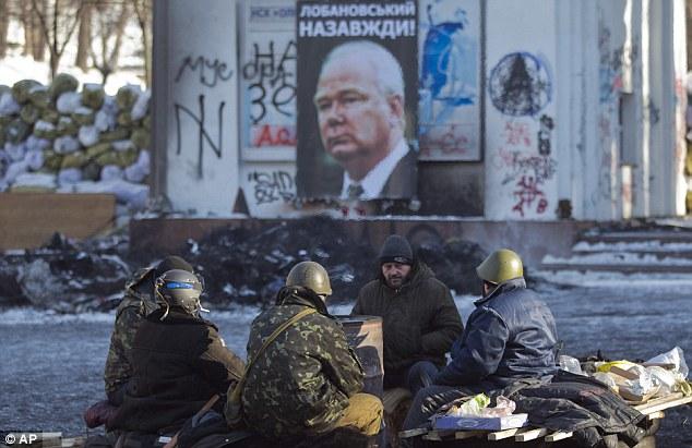 Protestos contra o ex-presidente Viktor Yanukovych com a foto do lendário técnico ucraniano ao fundo (Foto: AP)