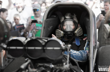 John Force warms his car up as fans look on
