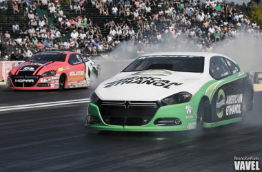 Two pro stock cars do its burnouts to warm up before making a run down the track.