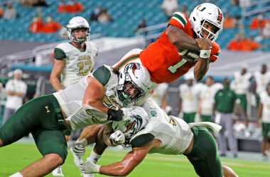 D'Eriq King runs with the ball and hurdles over a defender for the Miami Hurricanes against the UAB Trailblazers at Hard Rock Stadium in Miami Gardens, Florida/Miami Herald