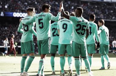 Varane y Vinicius Jr se chocan las manos junto al equipo / Foto: realmadrid
