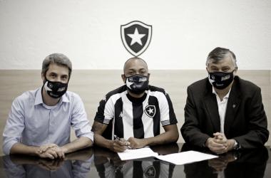Chay assina o novo contrato, ao lado de Eduardo Freeland e do presidente Durcésio Mello. (Foto: Vitor Silva/Botafogo)