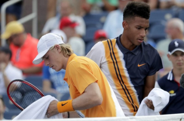 Denis Shapovalov (L) passes in front of Félix Auger-Aliassime after the conclusion of one of the changeovers during their first-round match at the 2018 U.S. Open. | Photo: Julio Cortez/AP