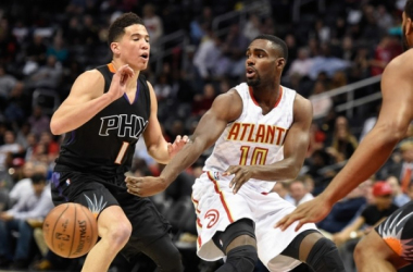 Atlanta Hawks guard Tim Hardaway Jr. (10) throws a pass by Phoenix Suns guard Devin Booker (1). | Dale Zanine-USA TODAY Sports