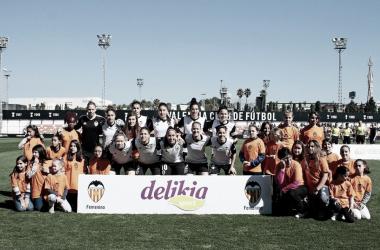 Las titulares del VCF Femenino posando con22 niñas de Escoles Cor Blanquinegre, proyecto educativo de la Fundació Valencia CF. Fuente: Valencia CF.