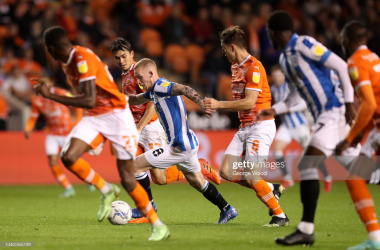 BLACKPOOL, ENGLAND - SEPTEMBER 14: Lewis O'Brien of Huddersfield Town runs with the ball whilst under pressure from Kenny Dougall and Ryan Wintle of Blackpool during the Sky Bet Championship match between Blackpool and Huddersfield Town at Bloomfield Road on September 14, 2021 in Blackpool, England. (Photo by George Wood/Getty Images)