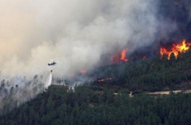 Vista de un helicóptero efectuando una descarga sobre el incendio forestal. Fotografía: EFE