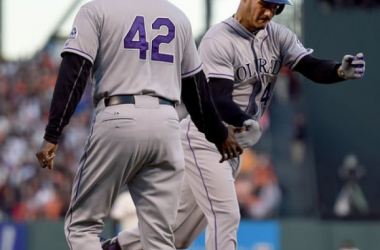 Nolan Arenado #28 of the Colorado Rockies is congratulated by third base coach Stu Cole #39 after Arenado hit a three-run homer against the San Francisco Giants in the top of the first inning at AT&T Park on April 15, 2015 in San Francisco,
