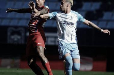 Kenedy contrala el balón ante Mejías. / Foto: Granada CF