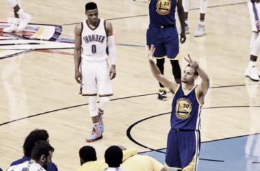 Curry señalando al público que se define en el séptimo juego; Westbrook, observa. / Foto: AP.