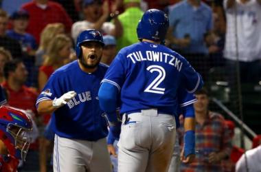 Troy Tulowitzki #2 of the Toronto Blue Jays celebrates with his teammate Dioner Navarro #30 after hitting a three run home run against Chi Chi Gonzalez #21 of the Texas Rangers in the sixth inning during game three of the American League Di