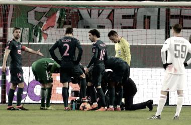 Filipe Luis, tendido en el suelo, rodeado por sus compañeros tras lesionarse en el partido ante el Lokomotiv de Moscú | UEFA