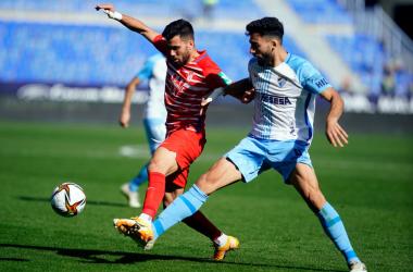 Fede Vico peleando un balón ante un jugador del Málaga. Foto: Pepe Villoslada / Granada CF.