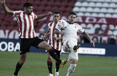 Leandro Diaz disputando la pelota con Bustos, jugador de Independiente.