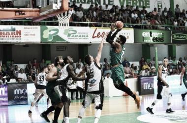 Smith volando ante la mirada de los jugadores de Olímpico. Foto: Prensa Estudiantes