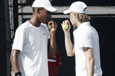 Félix Auger-Aliassime (L) and Denis Shapovalov discuss strategy between points during their first round doubles match against Bernard Tomic and Viktor Troicki at the 2016 Rogers Cup. | Photo: Max Gao
