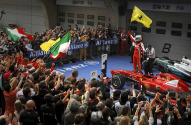 Alonso ergue bandeira da Ferrari, após a vitória: mais vivo do que nunca no Mundial de Pilotos (Fotos: Reuters)