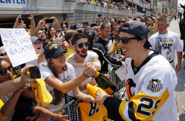 Associated Press HAPPY TIMES — Pittsburgh Penguins goalie Marc-Andre Fleury celebrates with fans during the Stanley Cup victory parade in Pittsburgh.