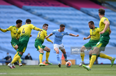 Phil Foden of Manchester City shields the ball from Kenny McLean of Norwich City during the Premier League match between Manchester City and Norwich City at Etihad Stadium on July 26, 2020 in Manchester, England. Football Stadiums around Europe remain empty due to the Coronavirus Pandemic as Government social distancing laws prohibit fans inside venues resulting in all fixtures being played behind closed doors. (Photo by Shaun Botterill/Getty Images)
