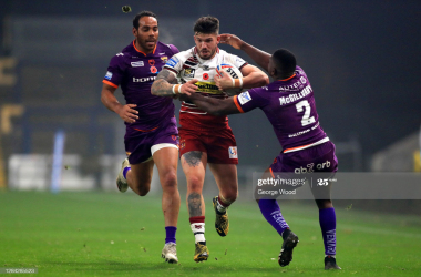LEEDS, ENGLAND - NOVEMBER 06: Oliver Gildart of Wigan Warriors is tackled by Jermaine McGillvary of Huddersfield Giants during the Betfred Super League match between Wigan Warriors and Huddersfield Giants at Emerald Headingley Stadium on November 06, 2020 in Leeds, England. Sporting stadiums around the UK remain under strict restrictions due to the Coronavirus Pandemic as Government social distancing laws prohibit fans inside venues resulting in games being played behind closed doors. (Photo by George Wood/Getty Images)