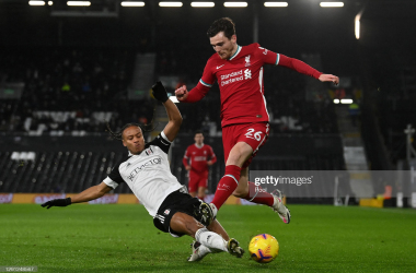 LONDON, ENGLAND - DECEMBER 13: Andrew Robertson of Liverpool is tackled by Bobby Decordova-Reid of Fulham during the Premier League match between Fulham and Liverpool at Craven Cottage on December 13, 2020 in London, England. A limited number of spectators (2000) are welcomed back to stadiums to watch elite football across England. This was following easing of restrictions on spectators in tiers one and two areas only. (Photo by Neil Hall - Pool/Getty Images)