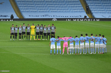 Manchester City and Newcastle United players stand for a minutes silence to remember the lives lost this year associated with football. (Photo by Peter Powell -Pool/Getty Images)