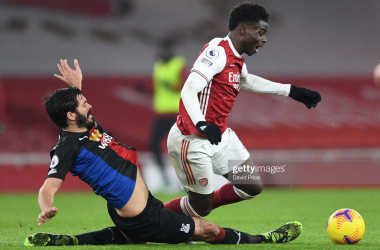 LONDON, ENGLAND - JANUARY 14: Bukayo Saka of Arsenal is challenged by James Tomkins of Palace during the Premier League match between Arsenal and Crystal Palace at Emirates Stadium on January 14, 2021 in London, England. Sporting stadiums around England remain under strict restrictions due to the Coronavirus Pandemic as Government social distancing laws prohibit fans inside venues resulting in games being played behind closed doors. (Photo by David Price/Arsenal FC via Getty Images)