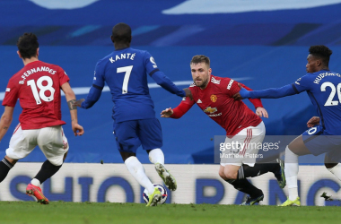 LONDON, ENGLAND - FEBRUARY 28: Luke Shaw of Manchester United in action with Ngolo Kante and Callum Hudson-Odoi of Chelsea during the Premier League match between Chelsea and Manchester United at Stamford Bridge on February 28, 2021 in London, England. Sporting stadiums around the UK remain under strict restrictions due to the Coronavirus Pandemic as Government social distancing laws prohibit fans inside venues resulting in games being played behind closed doors. (Photo by Matthew Peters/Manchester United via Getty Images)