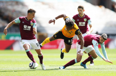 WOLVERHAMPTON, ENGLAND - APRIL 25: Adama Traore of Wolverhampton Wanderers is challenged by Matthew Lowton (R) and Ashley Westwood of Burnley during the Premier League match between Wolverhampton Wanderers and Burnley at Molineux on April 25, 2021 in Wolverhampton, England. Sporting stadiums around the UK remain under strict restrictions due to the Coronavirus Pandemic as Government social distancing laws prohibit fans inside venues resulting in games being played behind closed doors. (Photo by Jack Thomas - WWFC/Wolves via Getty Images)
