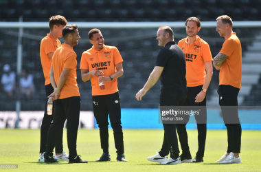 DERBY, ENGLAND - JULY 18: Ravel Morrison of Derby talks to manager Wayne Rooney and his teammates before the pre-season friendly match between Derby County and Manchester United at Pride Park on July 18, 2021 in Derby, England. (Photo by Nathan Stirk/Getty Images)