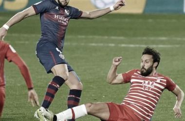 Germán haciendo una entrada a Rafa Mir en el partido del Huesca - Granada CF