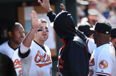 Baltimore Orioles' Chris Davis is congratulated by a team mate in the dugout after scoring against the Boston Red Sox in the seventh inning of a baseball game, Sunday, April 26, 2015, in Baltimore. The Orioles won 18-7. (AP Photo/Gail Burton)