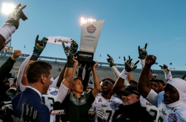 South Florida interim head coach T.J Weist holds up the Birmingham Bowl trophy after the Bulls' win over South Carolina | Source: Butch Dill - Associated Press
