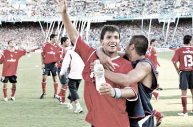 """Aguero celebra de cara a la hinchada de Independiente, abrazado por César """"Picante"""" Pereyra."""