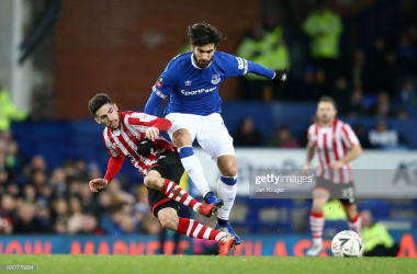 Andre Gomes of Everton and Tom Pett of Lincoln City in action during the FA Cup Third Round match between Everton and Lincoln City at Goodison Park on January 5. (Photo by Jan Kruger/Getty Images)<br>