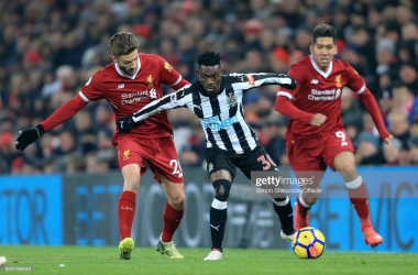 Christian Atsu of Newcastle battles with Adam Lallana and Roberto Firmino. (Photo by Simon Stacpoole/Offside/Getty Images)