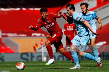 LIVERPOOL, ENGLAND - JULY 11: Kevin Long of Burnley puts pressure on Roberto Firmino of Liverpool during the Premier League match between Liverpool FC and Burnley FC at Anfield on July 11, 2020 in Liverpool, England. Football Stadiums around Europe remain empty due to the Coronavirus Pandemic as Government social distancing laws prohibit fans inside venues resulting in all fixtures being played behind closed doors. (Photo by Clive Brunskill/Getty Images)