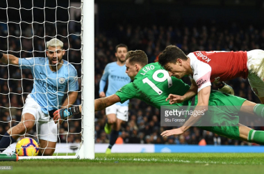Manchester City striker Sergio Aguero (l) looks on after scoring his hat trick goal despite the efforts of Arsenal goalkeeper Bernd Leno and Laurent Koscielny during the Premier League match between Manchester City and Arsenal FC at Etihad Stadium on February 03, 2019 in Manchester, United Kingdom. (Photo by Stu Forster/Getty Images)