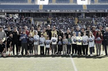 Parte de la plantilla posa con algunos alumnos que han visitado el entrenamiento | Foto: Málaga CF