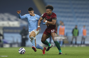 MANCHESTER, ENGLAND - MARCH 02: Adama Traore of Wolverhampton Wanderers and Joao Cancelo of Manchester City battle for possession during the Premier League match between Manchester City and Wolverhampton Wanderers at Etihad Stadium on March 02, 2021 in Manchester, England. Sporting stadiums around the UK remain under strict restrictions due to the Coronavirus Pandemic as Government social distancing laws prohibit fans inside venues resulting in games being played behind closed doors. (Photo by Clive Brunskill/Getty Images)