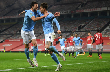 <div>MANCHESTER, ENGLAND - JANUARY 06: John Stones of Manchester City celebrates with teammate Ruben Dias after scoring his team's first goal during the Carabao Cup Semi-Final match between Manchester United and Manchester City at Old Trafford on January 06, 2021 in Manchester, England. (Photo by Shaun Botterill/Getty Images)</div>