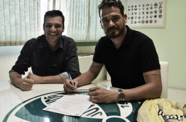 Jogador no momento da assinatura ao lado do vice-presidente de futebol, Jones Biglia (Foto: Divulgação / Juventude)
