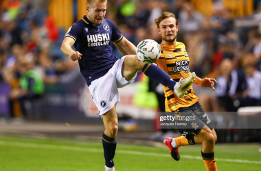 Billy Mitchell of Millwall battles for possession with Ben Worman of Cambridge United during the Carabao Cup Second Round match between Millwall and Cambridge United at The Den on August 24, 2021.(Photo by Jacques Feeney/Getty Images)