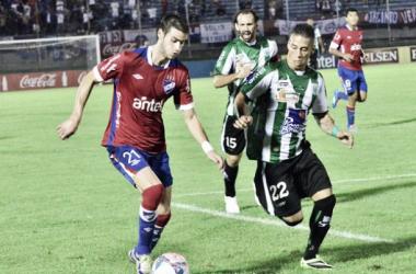 Gastón Pereiro lleva el balón, marcado por un defensor de Racing. Foto: Web oficial de Nacional