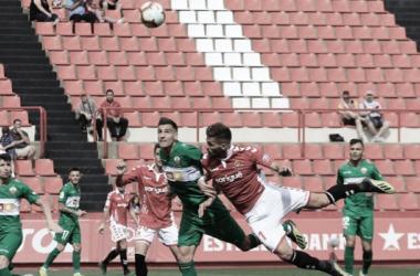 Fabián Noguera pugna por el esférico frente la atente mirada de los jugadores del Elche. LA LIGA.