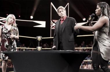 Ember Moon y Asuka firmando las confirmaciones del combate con William Regal como mediador | Fuente: WWE